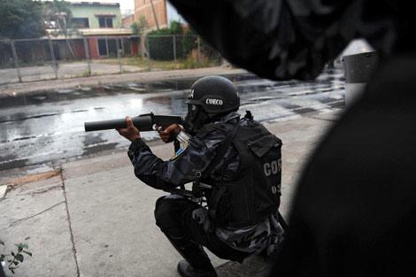 Un policía hondureño dispara gas lacrimógeno en Tegucigalpa. | AFP