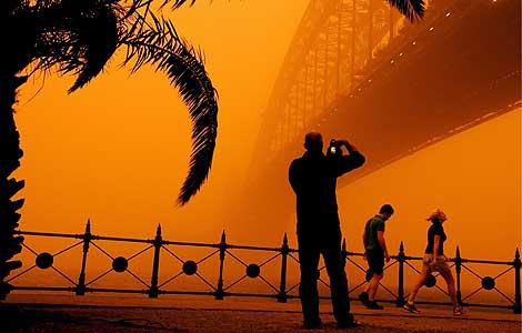 El puente de la bahía, envuelto por la nube de arena.   Efe