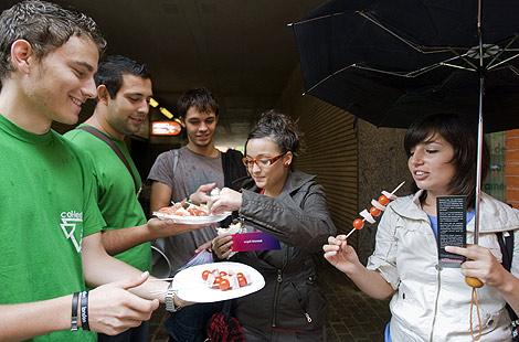 Reparto de brochetas de carne y pescado entre los jóvenes universitarios   Efe.