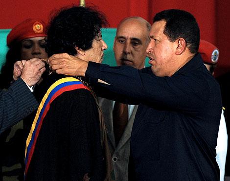 Chávez entrega un obsequio al líder libio. | Afp