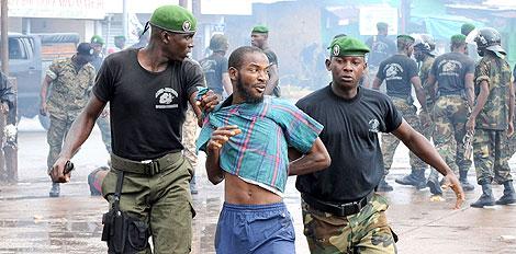 Dos policías guineanos detienen a un manifestante en Conakry. | AFP