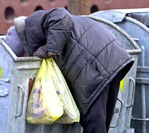 Una persona buscando en un cubo de basura