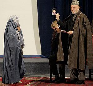 La mujer muestra las fotos a Karzai durante el acto de homenaje a las víctimas. | Reuters