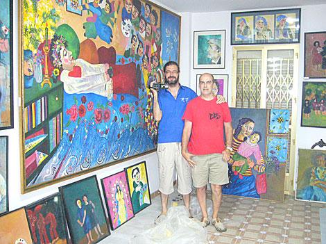 Los autores del mediometraje posando en una sala repleta de cuadros de Ocaña.