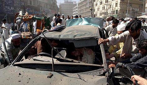 Varias personas intentan recuperar un cadáver en un vehículo tras el atentado. | Efe