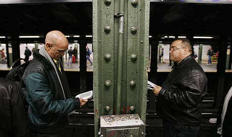Lectores de libros electrónicos en el Metro de Nueva York.   Reuters