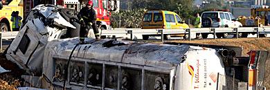 Un bombero trabaja subido en el camión siniestrado. | Efe