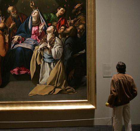 Un hombre observa uno de los cuadros de la exposición. | Afp