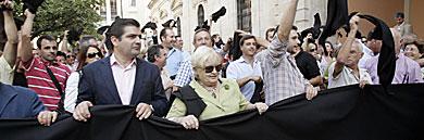 Comerciantes, con pañuelos negros, a las puertas del Ayuntamiento. | J. Morón