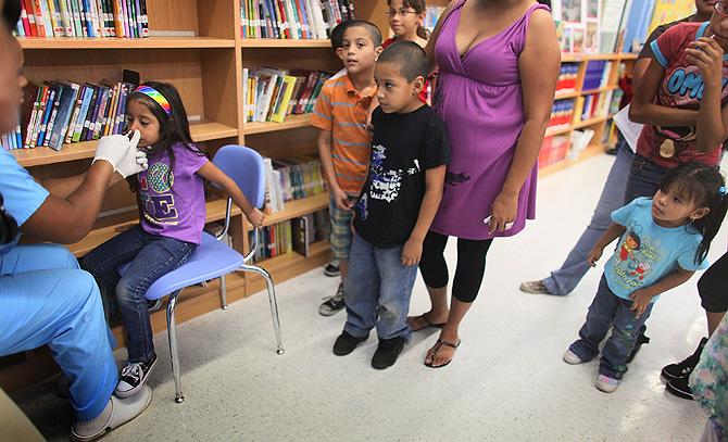 Un grupo de niños recibe la vacuna de la gripe A en una escuela de Miami. | AFP