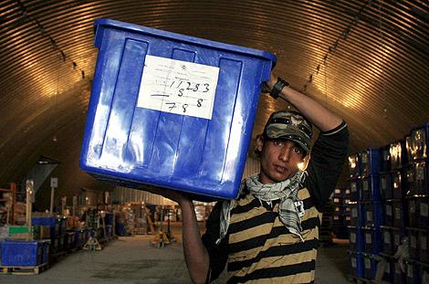 Trabajadores de la Comisión Electoral trasladan las urnas.   Efe