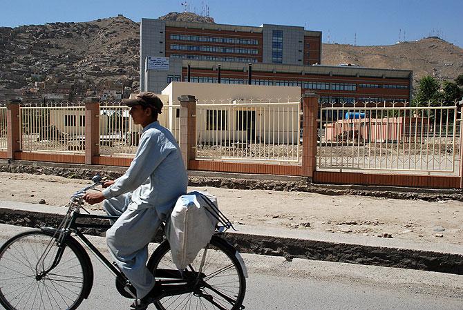 Un joven pasa en bicicleta por delante de los dos edificios del hospital, en el centro de Kabul. | Mònica Bernabé