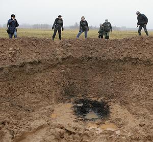 Varias personas observan el cráter. | Efe