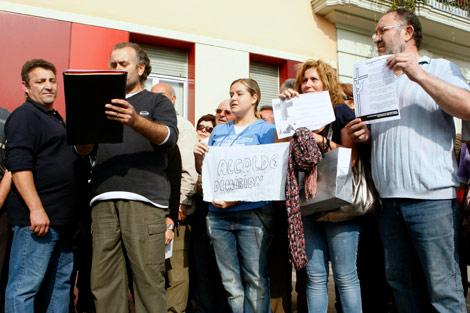 Algunos de los vecinos protestan en la entrada del Ayuntamiento. | Efe