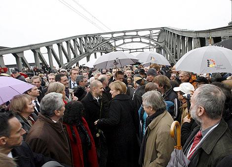 Merkel cruza simbólicamente el antiguo paso fronterizo de la calle Bornholm en Berlín.   Efe