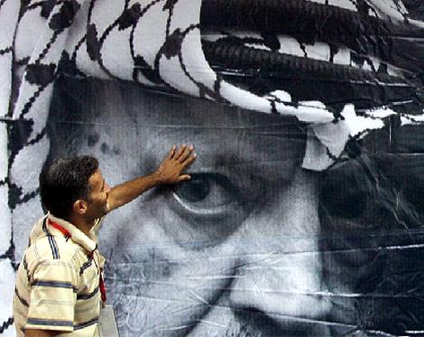 Un hombre coloca un cartel conmemorativo con la imagen de Arafat. | Efe