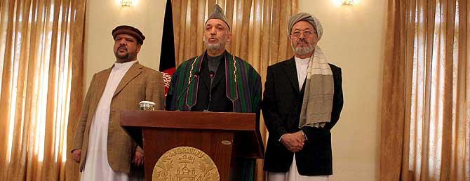 Hamid Karzai, flanqueado por los dos señores de la guerra, en la rueda de prensa. | Efe (Sabawoon)
