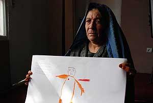 Alia muestra la ilustración que ha hecho sobre su hijo muerto. | M. Bbernabé