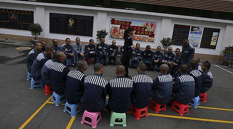 Una funcionaria de prisiones habla a un grupo de presos en la cárcel legal de Jinjiang. | Ap