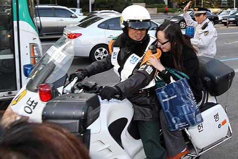 Un policía ayuda a una estudiante a llegar a tiempo al examen.   Efe
