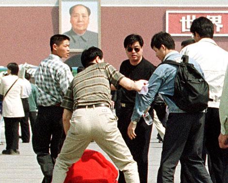 Policías de paisano detienen a un miembro de Falun Gong (dcha., con bolsa)tras una marcha en la Plaza de Tiannanmen en 2000. | AP