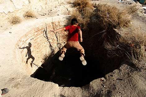 Un crío salta a un pozo repleto de cubiertas de plástico de cables de cobre. | S. González