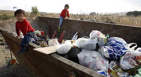 Dos niños, en uno de sus patios de recreo: un contenedor repleto de basura. | Sergio González