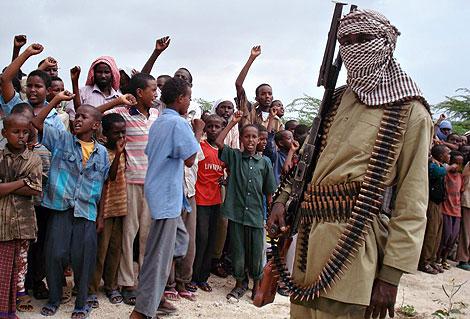 Niños somalíes cantan consignas favorables a Al Shabab, ante uno de sus miembros. | Afp