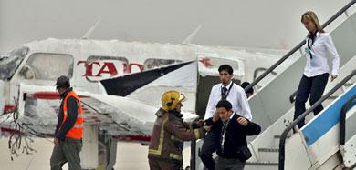 Los bomberos sacan a figurantes del avión.   Efe