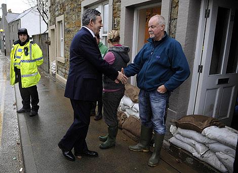 Gordon Brown saluda a uno de los afectados por las inundaciones en el noroeste de Inglaterra. | Reuters