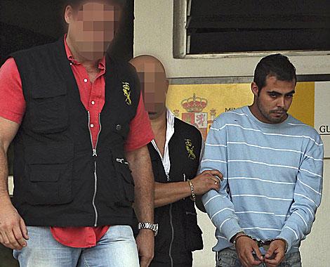 Dos agentes trasladan al detenido por la muerte de una niña en Tenerife. | Efe