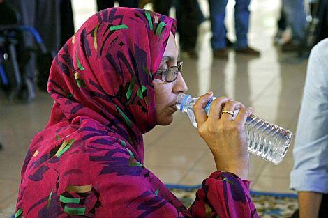 Aminatu Haidar, muy débil, bebe agua en el aeropuerto de Lanzarote.   Efe