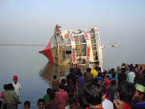 Curiosos observan el ferry que volcó posiblemente por el exceso de pasajeros. | AFP