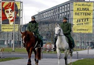 Dos policías pasan junto a carteles de Greenpeace que reclaman resultados palpables en la Cumbre de Copenhague.| Efe