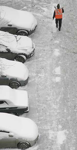 Un operario municipal pasa junto a varios coches cubiertos por la nieve en Moscú. | AFP