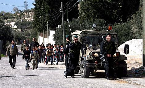 Soldados israelíes observan el paso de unos estudiantes palestinos   Efe