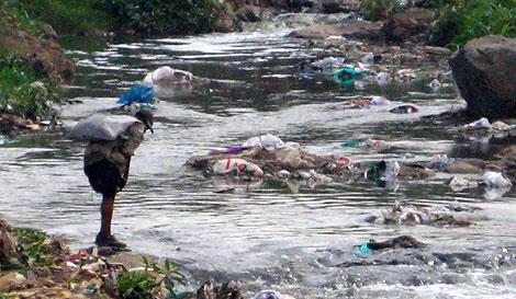 Un hombre intenta 'bañarse' en el río, lleno de basura. | J. Socías
