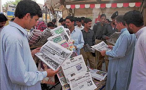 Un grupo de ciudadanos leen el periódico en una especie de quiosco. (Foto: Mian Kurshid/Afp).