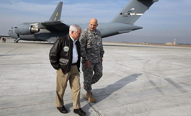 El secretario de Defensa, Robert Gates (izqda.), en Bagdad, ante un C-17. | Reuters