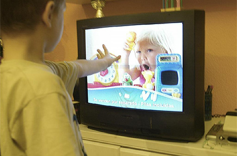 Un niño, delante de una televisión con publicidad en emisión. (Foto: Julio Palomar)