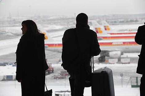 Pasajeros observan el aspecto de las pistas nevadas de Barajas. | Antonio M. Xoubanova