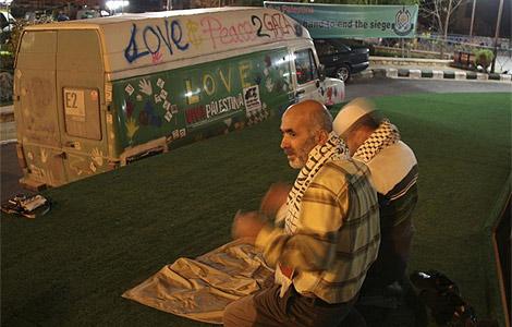 Dos hombres rezan junto a una furgoneta de ayuda humanitaria.| Reuters
