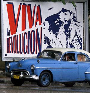 Un coche General Motors Oldsmobile junto a un cartel revolucionario en una calle de La Habana. (Foto: AP)