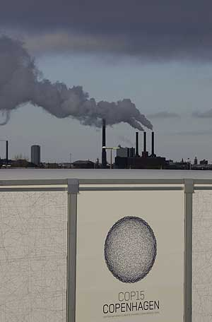 Cartel anunciando la cumbre de Copenhague, con una factoría al fondo. | Ap