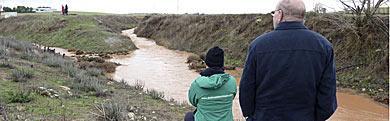 Dos personas observan el río Azuer.   Efe