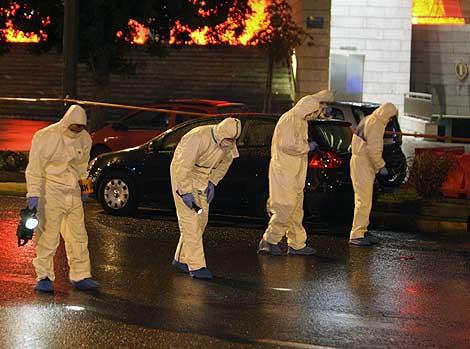 Policías antiterroristas buscan restos del artefacto explosivo.   Ap