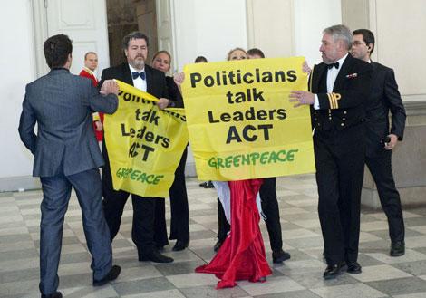 Juan López de Uralde, a la izquierda con barba, muestra una pancarta. | AFP