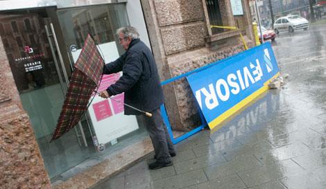 Un ciudadano pasa junto al cartel caído.   Jordi Avellà