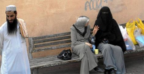 Dos mujeres y un hombre en una calle de Vic.