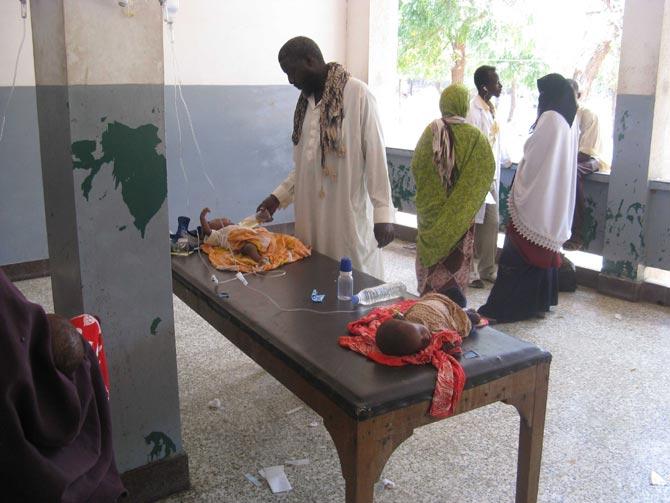 Un médico de Banaadir atiende a dos niños enfermos en una mesa.| H. Nour